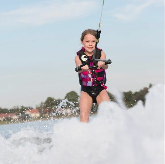 Young girl waterskiing while wearing a Connelly vest