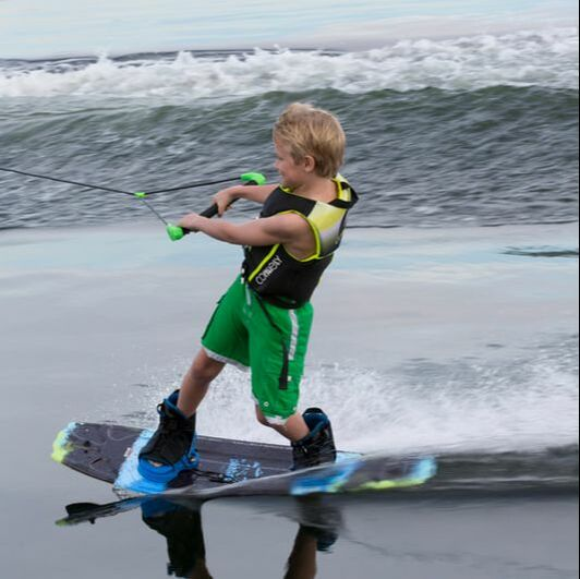 Young boy wake boarding on a Connelly board and wearing a Connelly vest